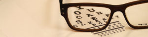 Picture of eyeglasses laying on a vision exam chart